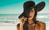Portrait of fashion young woman posing against sea wearing a black straw hat. Sensual girl covering half face with hat on beach with copy space. Attractive girl looking at camera with sea in backgroun