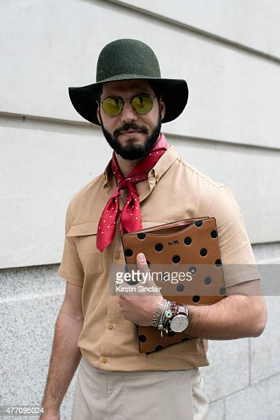Fashion writer for I'Officiel homme Kadu Dantas wears a Topman hat Gant scarf Coach New York purse Ray Ban sunglasses on day 2 of London Collections...
