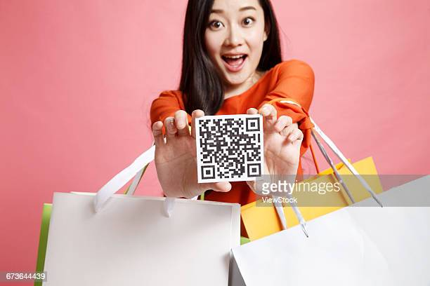 Fashion young woman holding a two-dimensional code