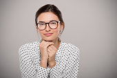 Young woman wearing modern eyeglasses anf thinking isolated on grey background with copy space. Portrait of smiling fashion student wearing big glasses. Proud young businesswoman with spectacles looki