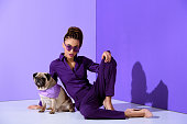 fashionable african american girl posing in purple suit with pug, ultra violet trend