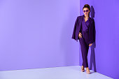 fashionable african american girl posing in trendy purple suit, ultra violet trend