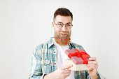 Fashionable bearded hipster guy in eyewear, opens wrapped present, recieves surprise from wife, being in good festive mood, isolated over white background. People, surprisment and presents concept.