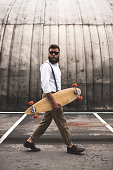 fashionable bearded man in sunglasses walking with longboard on parking place