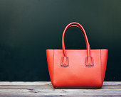 Fashionable beautiful big red handbag standing on a wooden floor on black wall background
