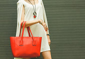 Fashionable beautiful big red handbag on the arm of the girl in a fashionable white dress, posing near the wall on a warm summer night. Warm color.