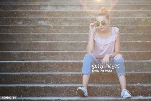 Fashionable beautiful woman sitting on stairs and posing