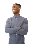 Portrait of a fashionable black guy smiling with arms crossed on isolated white background