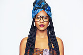 Head and shoulders portrait of fashionable young black woman in ethnic clothes with blue headscarf