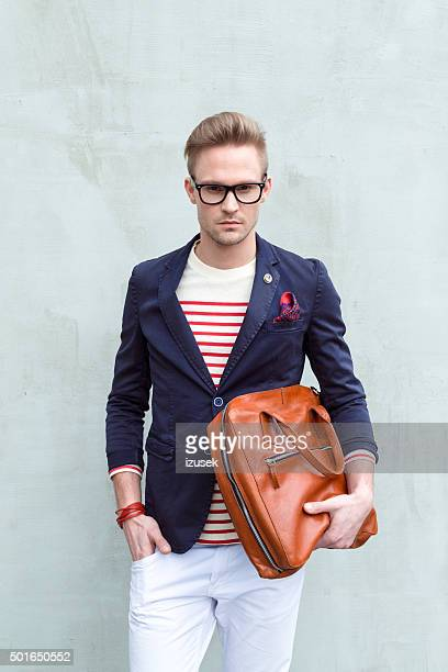 Fashionable blonde young man holding leather bag