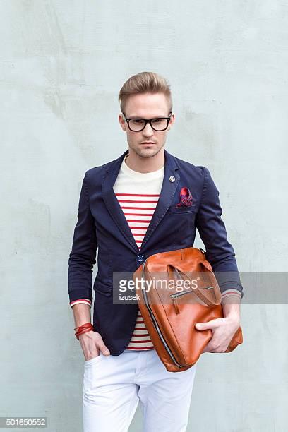Modische blonde junger Mann hält Leder-Tasche
