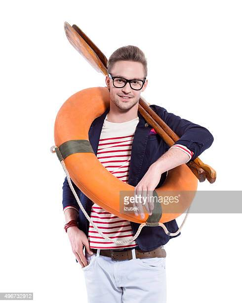 Fashionable blonde young man holding oars and lifebuoy