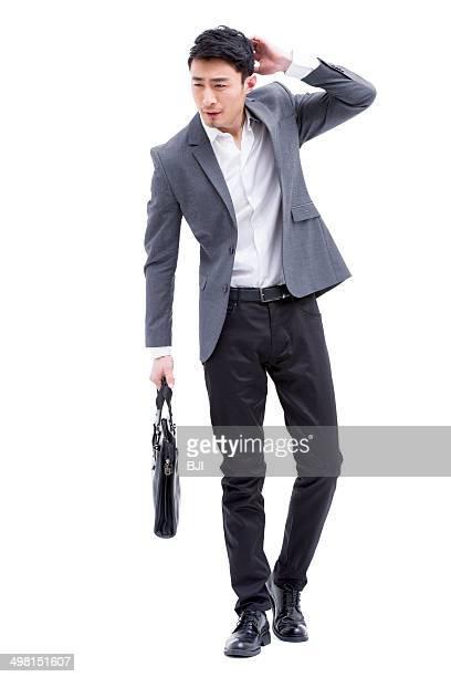 Fashionable businessman scratching head