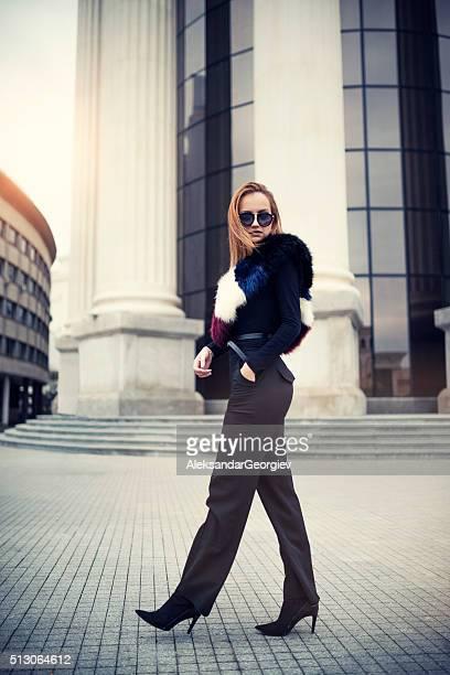 Elegante Geschäftsfrau mit Sonnenbrille zu Fuß im Freien auf der Stadt-Straße