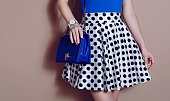 Fashionable girl in polka dots dress with blue bag . Beige background
