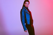 fashionable beautiful girl posing in leather jacket, on pink