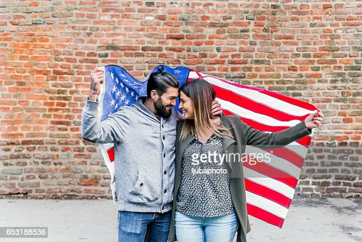 Fashionable hip couple in front of American flag New York : ストックフォト