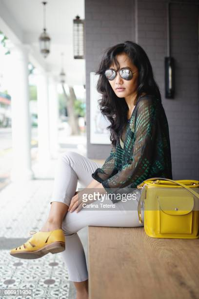 Fashionable Indonesian woman sitting along the street