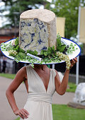 A fashionable lady wears a hat shaped like a blue stilton cheese during Ladies Day at Royal Ascot racecourse on June 19 2008 in Ascot England