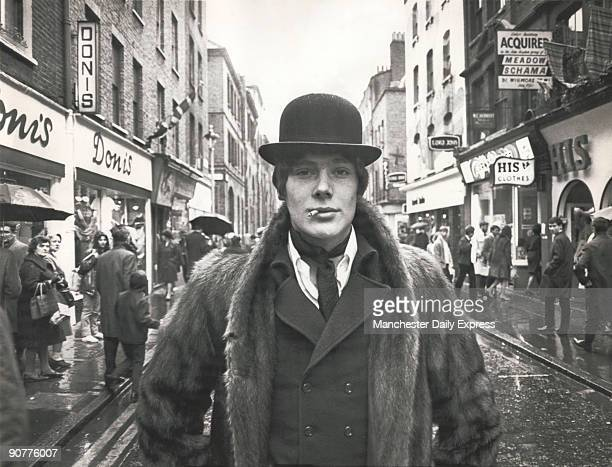 Fashionable male wearing a bowler hat and fur coat standing in the middle of the road on Carnaby Street in London in the heart of the Swinging Sixties
