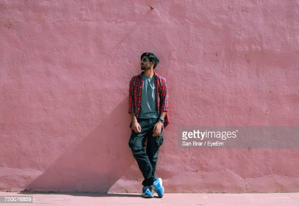 Fashionable Man Standing Against Pink Wall