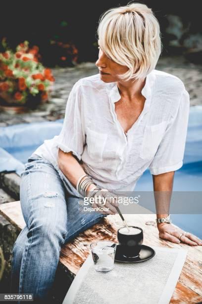 Fashionable mature beautiful blonde woman having coffee break outdoor