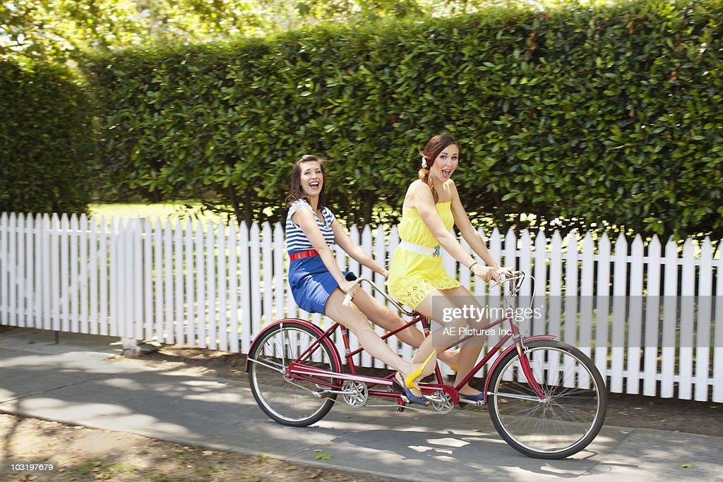 Fashionable pair ride tandem bike : Stock Photo