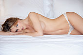 Fashionable photo of young topless woman on bed