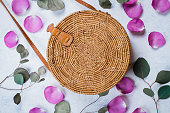 Fashionable rattan bag, flowers rose petals and eucalyptus leaves on light background. Copy space, top view