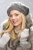 Fashionable Teenage Girl Wearing Cap And Fur Coat In Studio With Snow