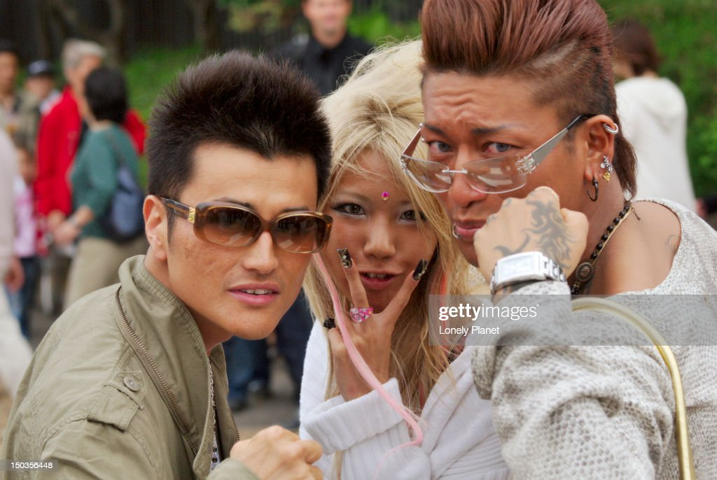 Fashionable teenagers making rude gestures, Shibuya. : Stock Photo