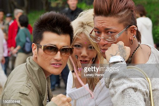 Fashionable teenagers making rude gestures, Shibuya. : Stock Photo