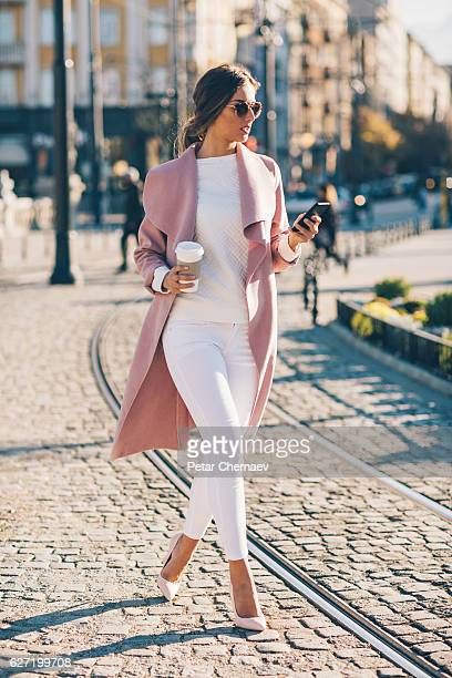 Fashionable woman dialing on the street