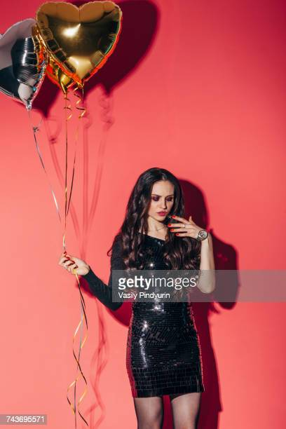 Fashionable woman holding helium balloons against coral background