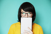Fashionable woman holding her ipad over her lips