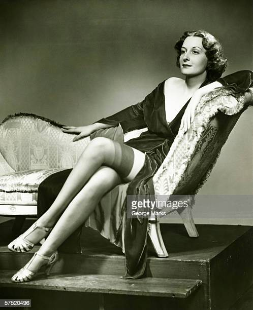 Fashionable woman in stockings sitting on chaise longue, (B&W), portrait