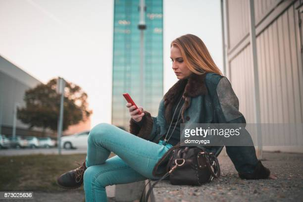 Fashionable woman using phone during autumn day