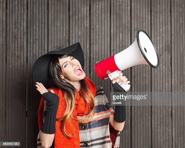 Modische Frau mit Herbst-poncho und Hut schreit mit Megafon