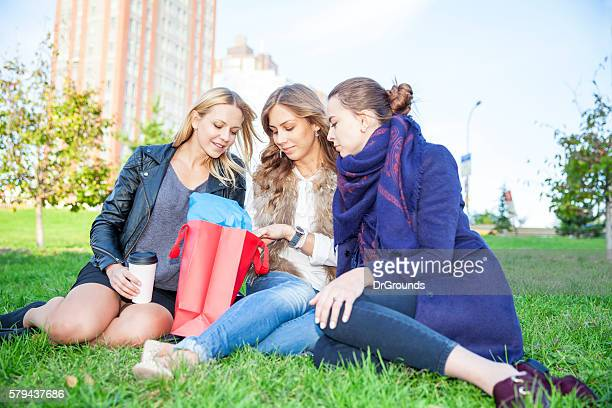 Fashionable women checking purchases in shopping bag outdoors