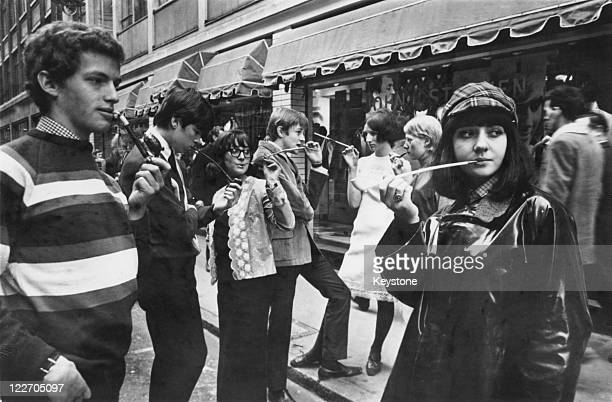 Fashionable young Londoners smoking pipes and cigarettes in long holders on a street in Soho 9th February 1965 The craze began when a mod asked local...