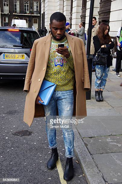 Fashionable young man reads his messages on a cellphone in the street in London