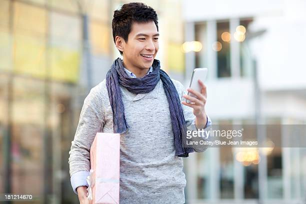 Fashionable young man with gift checking smart phone