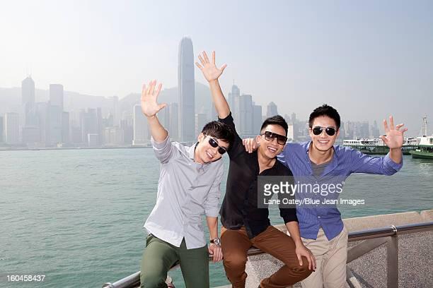 Fashionable young men enjoying the beautiful moment in Victoria Harbor, Hong Kong