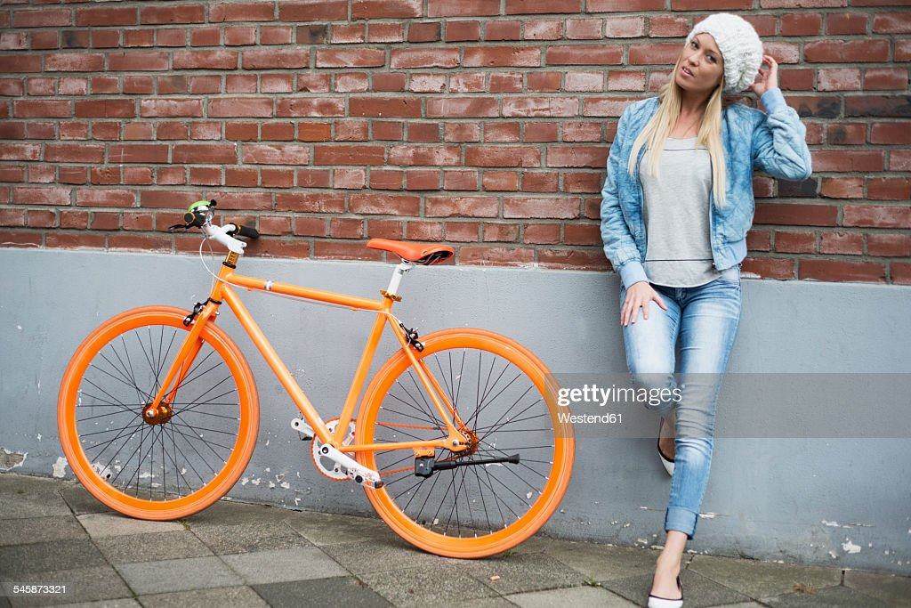 Fashionable young woman leaning at brick wall beside orange bicycle