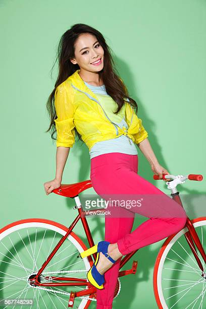 Fashionable young woman leaning on a bicycle