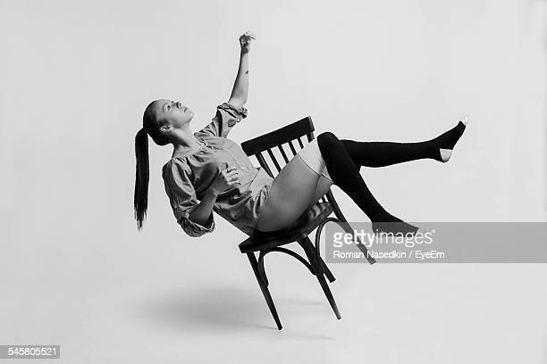 Fashionable Young Woman Looking Up While Sitting On Chair