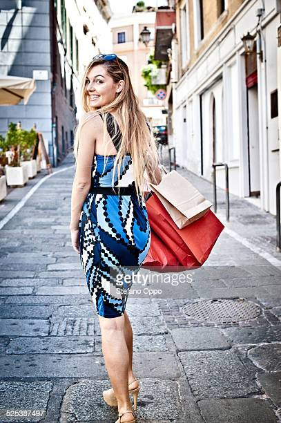 Fashionable young woman out shopping looking over her shoulder, Cagliari, Sardinia, Italy