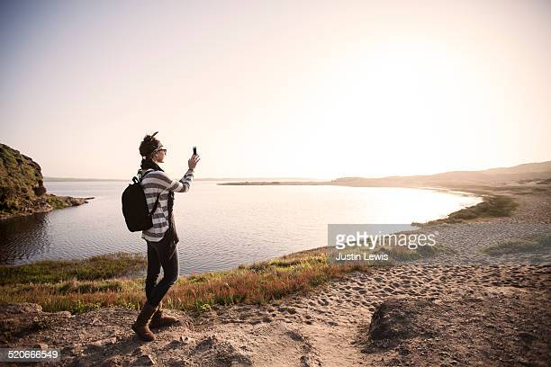Fashionable young woman takes self-pic at estuary