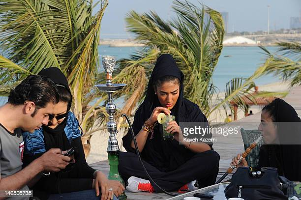 Fashionable young women drink nonalcholic Mochitos and smoke waterpipe while sat in a coffee shop on the sea front in the late afternoon hours on...