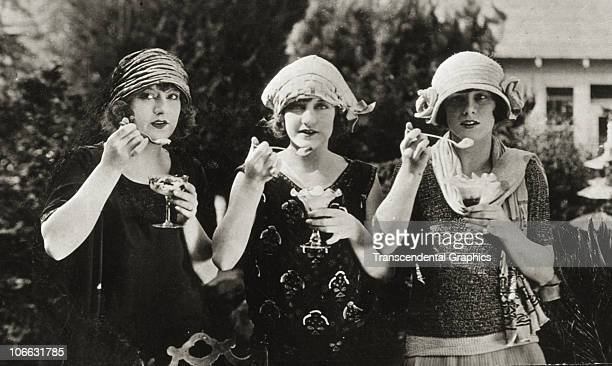 Fashionably dressed lovely young triplets enjoy ice cream as the unknown photographer snaps their picture circa 1920